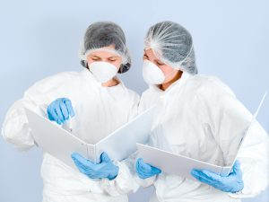 Two lab technicians in scrubs read out of binders