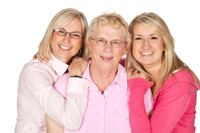 Two grown daughters embrace their elderly mother