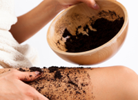 Woman rubbing coffee grounds on her thighs